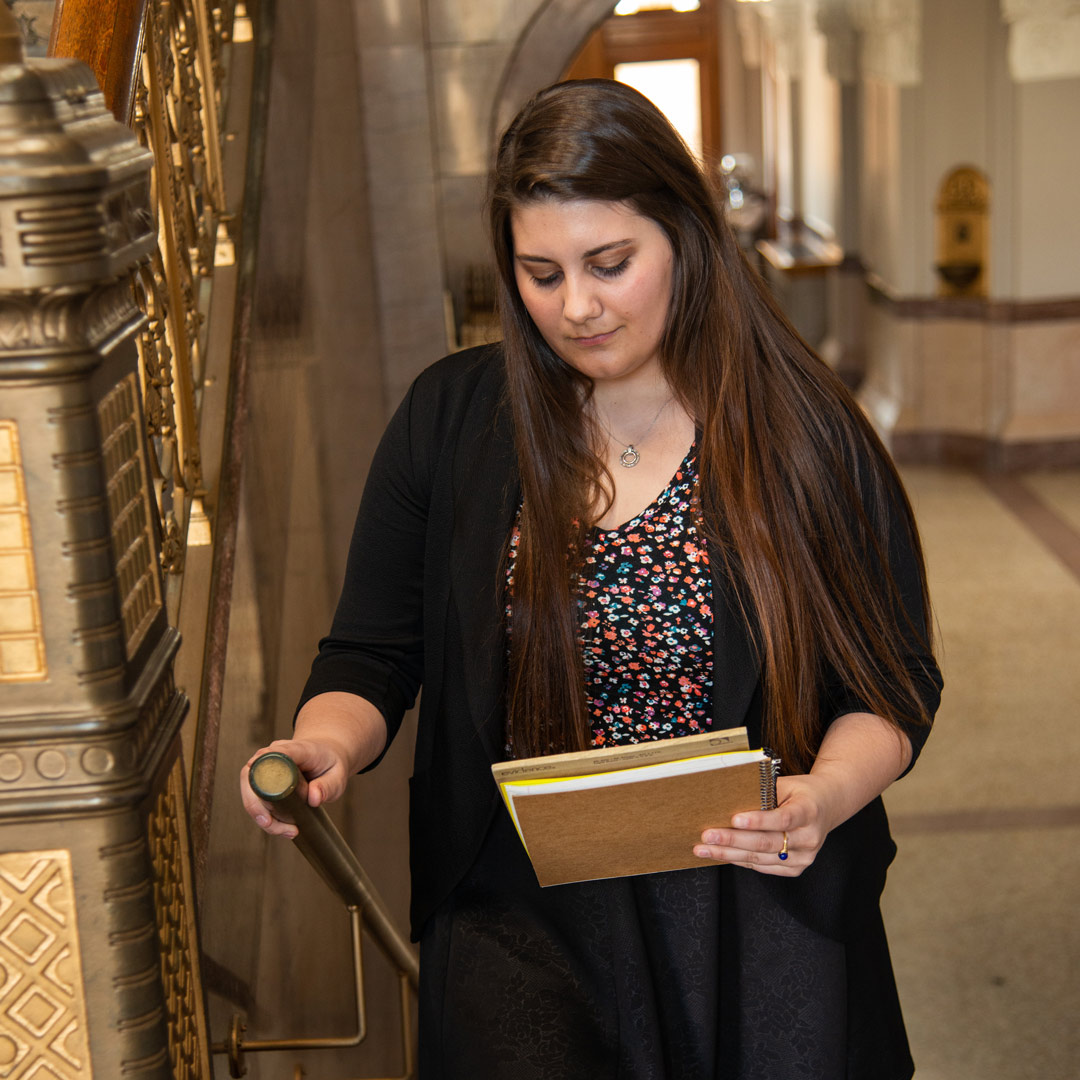 Caysey Farmer examining some documents while walking up stairs in the Rush County courthouse.
