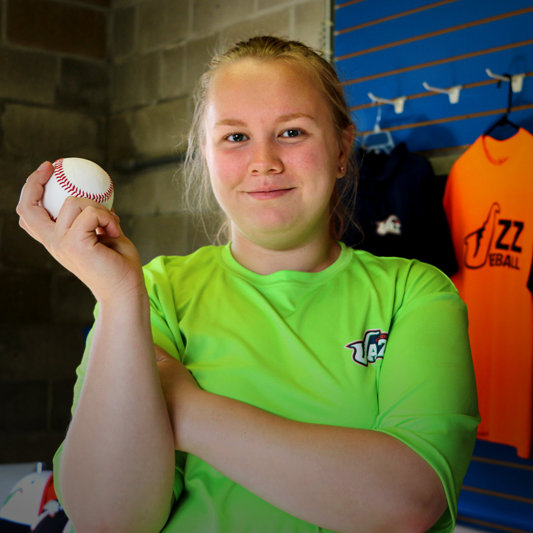 Tiani Christian smiling and holding a baseball in the Richmond Jazz baseball team ticket booth.